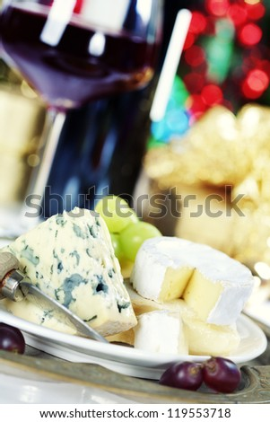 Cheese and wine on Christmass tree background - stock photo