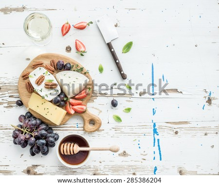 Cheese appetizer selection or wine snack set. Variety of cheese, grapes, pecan nuts, strawberry and honey on round wooden board over rustic white backdrop, top view, copy space - stock photo