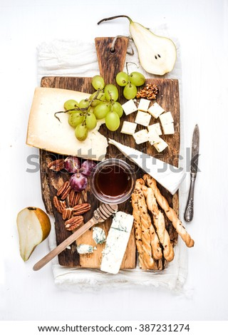 Cheese appetizer set. Various types of cheese, honey, grapes, pear, nuts and bread grissini sticks on rustic wooden board over white background, top view - stock photo