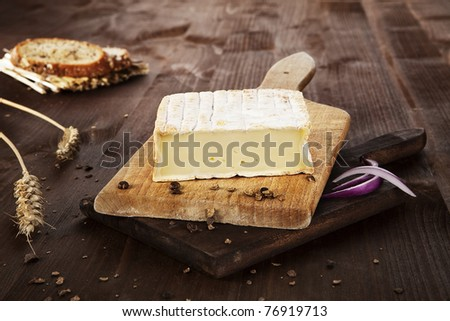 Cheese arranged on wooden board with bread, pepper corns and wheat. Agricultural vintage style concept. - stock photo