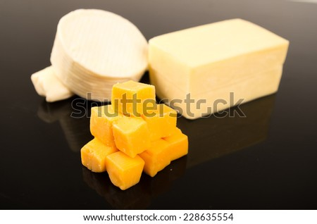 cheese assortment cheddar herbs fresh mozzarella on black table - stock photo