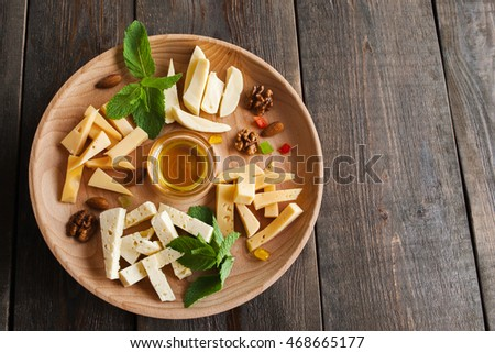 Cheese assortment plate on dark wooden background, free space. Top view on plate with snack on for wine with honey on round catering platter
