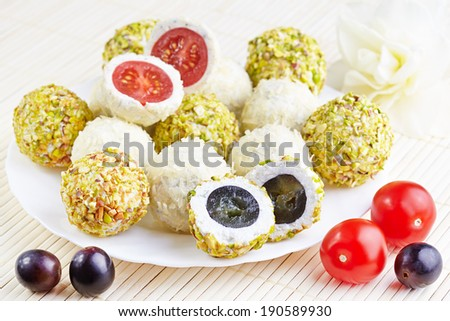 Cheese balls with a tomato and grapes inside - stock photo