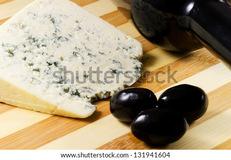 Cheese ,black olives  and red wine on a wooden plate - stock photo