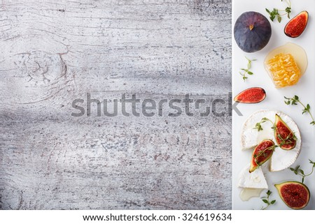 Cheese Board,appetizer.Brie cheese,figs,blueberries,honey and thyme.Copy space.selective focus - stock photo