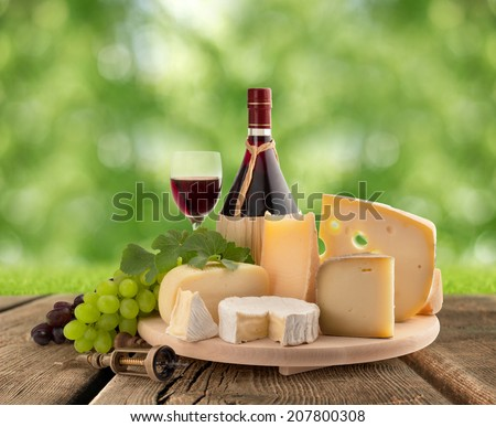 cheese board, grape and red wine on wooden table - stock photo