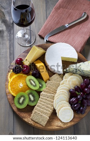 Cheese board with crackers, fruit and wine - stock photo
