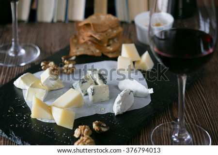 Cheese board with hard cheeses, camembert, blue cheese, nuts and crackers. Glasses of red wine and books a background
