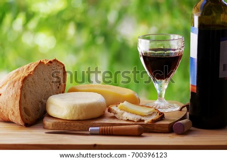 cheese, bread, and red wine on table
