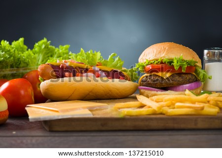 cheese burger and hot dogs with plenty of fast foods ingredients on the background - stock photo