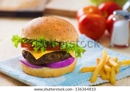 cheese burger , french fries and fast food with plenty of raw materials on the background - stock photo