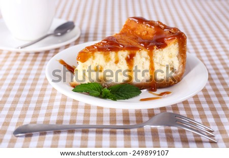 Cheese cake and cup of coffee on tablecloth closeup