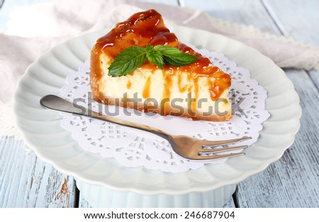 Cheese cake on paper napkin on plate on wooden background - stock photo