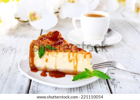 Cheese cake, orchids and cup of coffee on wooden background - stock photo