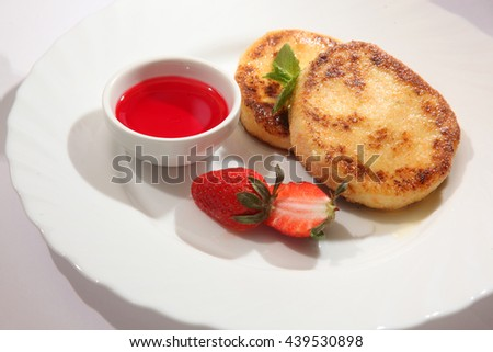 cheese cakes with sweet red sauce and strawberries - stock photo