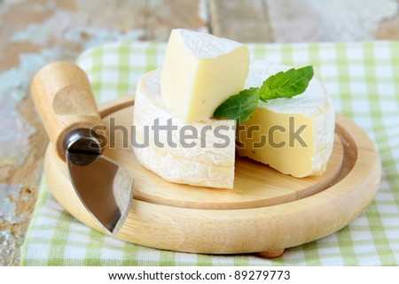 Cheese camembert on a wooden plate and  herbs - stock photo