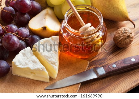 Cheese Camembert with honey, pear, walnut and grapes - stock photo