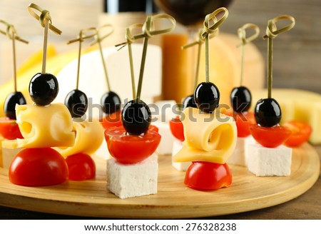 Cheese canapes with cherry tomatoes and olives on table close up - stock photo