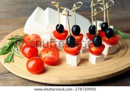 Cheese canapes with cherry tomatoes and olives on wooden tray close up - stock photo