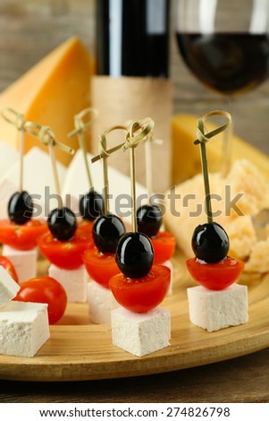 Cheese canapes with wine on table close up - stock photo