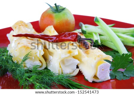 cheese cannelloni served with pepper and tomato on red plate