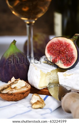 Cheese, figs and white wine on a table - stock photo