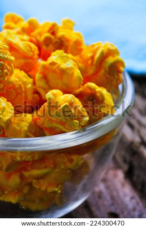 Cheese flavored popcorn in bowl on wooden table - stock photo