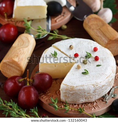 Cheese, grapes and herbs on a wooden board.
