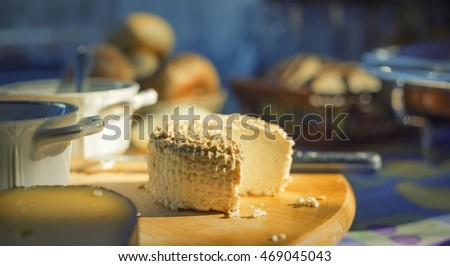 Cheese head on the board wooden in sunlight rays, breakfast.
