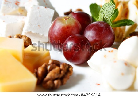 Cheese in the assortment of grapes and walnuts. Dairy produce