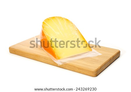 Cheese in vacuum packing on cutting board against white background - stock photo