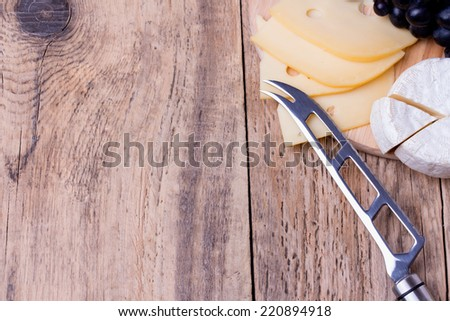 Cheese knife and various types of cheese on wooden background with copyspace - stock photo
