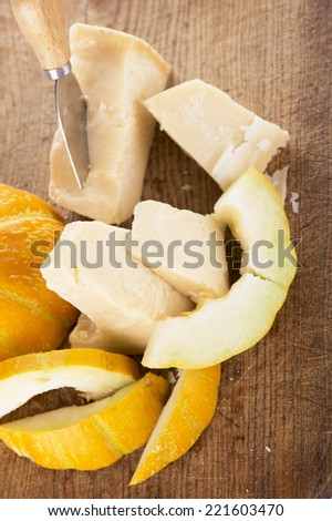 cheese, melon on wooden background
