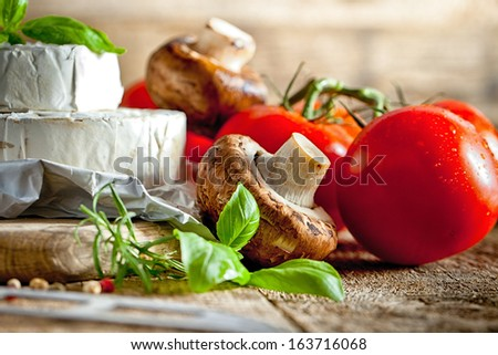 Cheese, mushrooms and aromatic herbs on old wooden background - stock photo