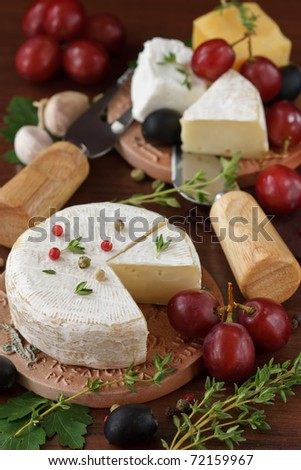 Cheese, olive and grapes on a wooden table.