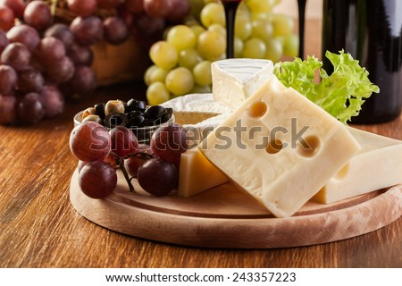 Cheese, olive and grapes on wooden board
