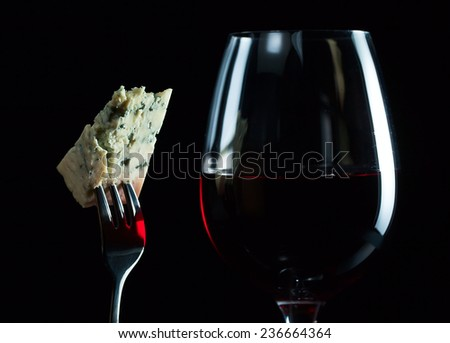 Cheese on a fork and red wine on black background - stock photo