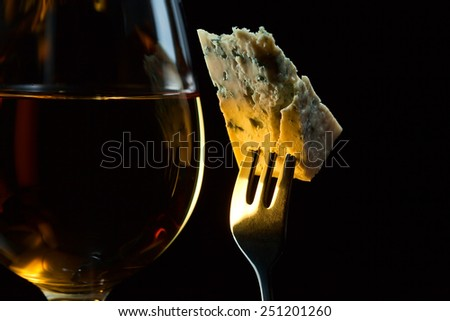 Cheese on a fork and  wine on black background