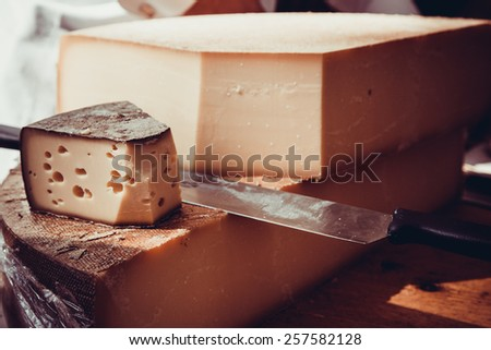 cheese on a wooden table with knife - stock photo