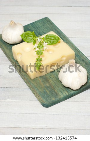 cheese on wooden board with blossoming basil and garlic bulbs, bright wooden table