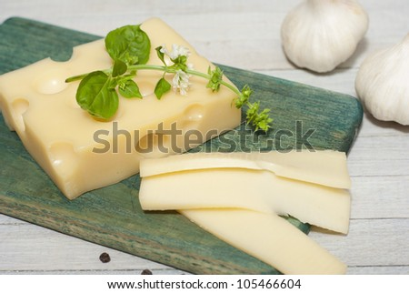 cheese on wooden board with blossoming basil and garlic cloves, bright wooden table