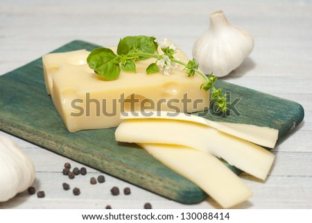 cheese on wooden board with blossoming basil and garlic cloves, bright wooden table - stock photo