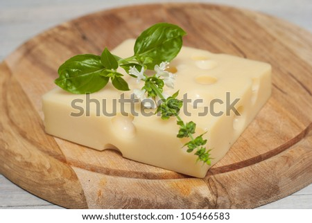 cheese on wooden board with blossoming basil, bright wooden table