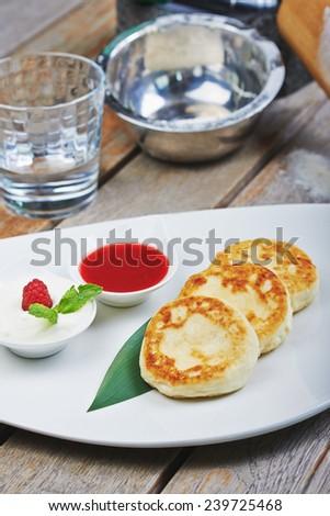 Cheese pancake, syrniki with raspberry syrup - stock photo
