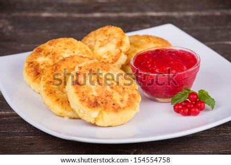 Cheese pancakes with berry jam in white plate - stock photo