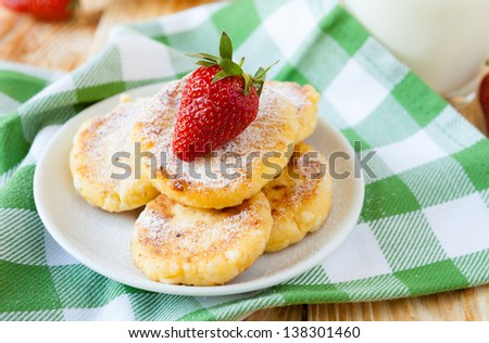 cheese pancakes with powdered sugar and strawberries, closeup - stock photo