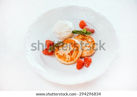 cheese pancakes with raspberries and cream - stock photo