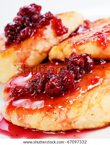 Cheese pancakes with raspberry jam on white plate