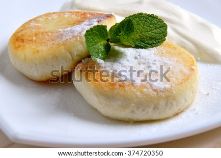 Cheese pancakes with sour cream - stock photo