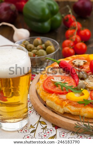 Cheese, pepperoni and tomato pizza with a glass of beer - stock photo